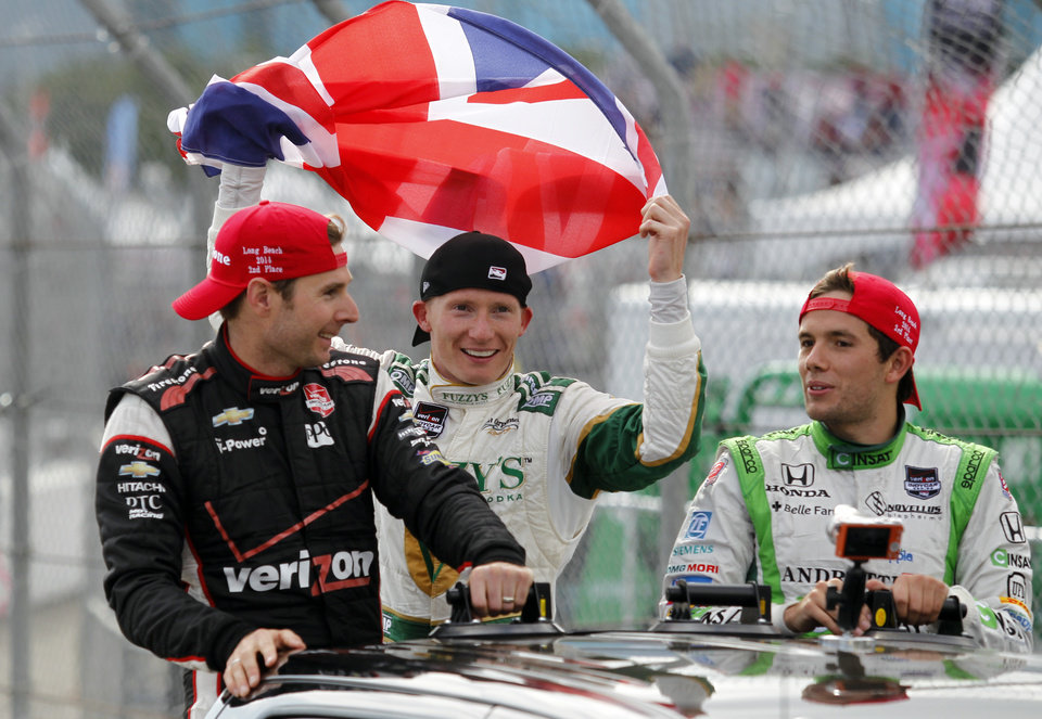 Photo - Winner Mike Conway, center, of England, holds up his country's flag on the victory lap with second-place Will Power, left, of Australia, and third-place Carlos Munoz, right, of Colombia, after the IndyCar Grand Prix of Long Beach auto race Sunday, April 13, 2014, in Long Beach, Calif. (AP Photo/Alex Gallardo)