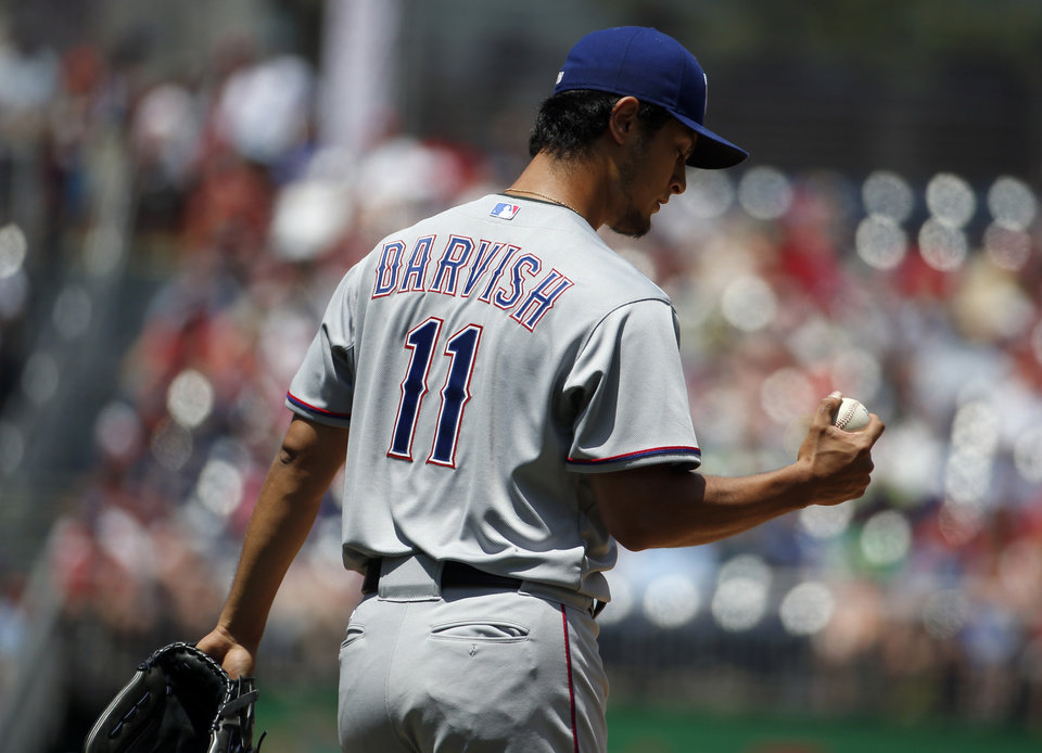 Photo - Texas Rangers starting pitcher Yu Darvish (11) looks at the ball between pitches during the first inning of a baseball game against the Washington Nationals, Sunday, June 1, 2014, in Washington. (AP Photo/Alex Brandon)