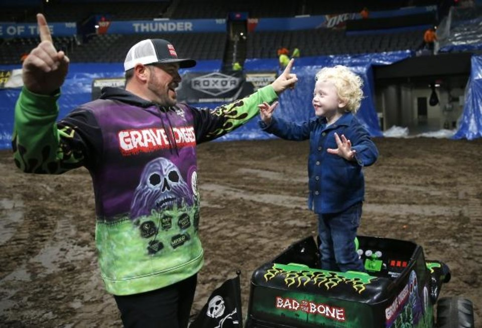 Photo -  Monster Jam driver Grave Digger, Brandon Vinson, celebrates with Ryker Ammons, 4, of Yukon, Okla., after driving around the track at Chesapeake Energy Arena in Oklahoma City, Friday, Feb. 14, 2020.  [Sarah Phipps/The Oklahoman]