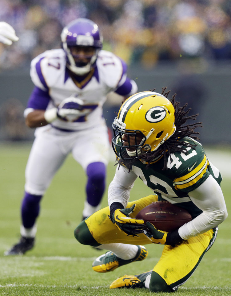 Photo - Green Bay Packers free safety Morgan Burnett (42) intercepts a pass during the second half of an NFL football game against the Minnesota Vikings Sunday, Dec. 2, 2012, in Green Bay, Wis. The Packers won 23-14. (AP Photo/Morry Gash)