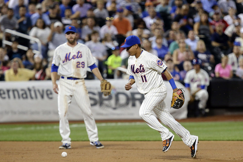 Photo - New York Mets shortstop Ruben Tejada (11) makes a fielding error to  let Atlanta Braves' Evan Gattis get safely to first on a single in the third inning of a baseball game, Wednesday, Aug. 27, 2014, in New York. Braves' Freddie Freeman scored on the hit. (AP Photo/John Minchillo)
