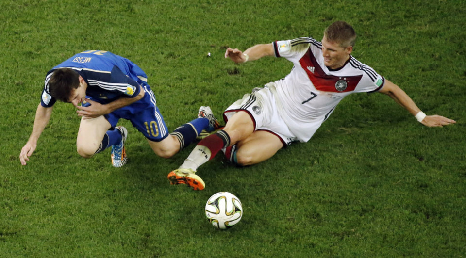 Photo - Germany's Bastian Schweinsteiger, right, tackles Argentina's Lionel Messi during the World Cup final soccer match between Germany and Argentina at the Maracana Stadium in Rio de Janeiro, Brazil, Sunday, July 13, 2014. Mario Goetze volleyed in the winning goal in extra time to give Germany its fourth World Cup title with a 1-0 victory over Argentina on Sunday. (AP Photo/Fabrizio Bensch, Pool)