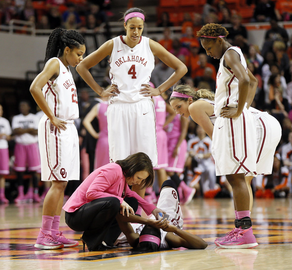 Photo - From left, Oklahoma's Gioya Carter (25), Nicole Griffin (4), Morgan Hook (10) and Sharane Campbell (24) watch athletic trainer Carolynn Loon attend to Aaryn Ellenberg (3) after she was injured in the second half during the women's Bedlam college basketball game between the OU Sooners and the OSU Cowgirls at Gallagher-Iba Arena in Stillwater, Okla., Sunday, Feb. 16, 2014. OSU won, 73-57. Photo by Nate Billings, The Oklahoman