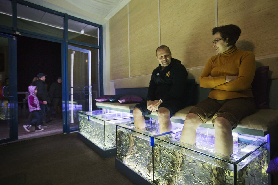 Photo - Olga, right, and Oleg Khrushcheva, visiting from Moscow, sit for a fish pedicure at a foot spa on the promenade along the Black Sea, Saturday, Feb. 15, 2014, in central Sochi, Russia, home of the 2014 Winter Olympics. (AP Photo/David Goldman)