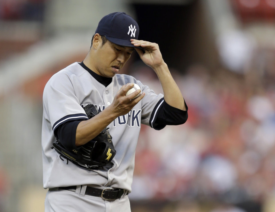 Photo - New York Yankees starting pitcher Hiroki Kuroda adjusts his cap during the first inning of a baseball game against the St. Louis Cardinals on Wednesday, May 28, 2014, in St. Louis. (AP Photo/Jeff Roberson)