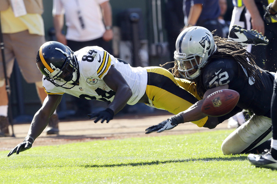 Photo -   Pittsburgh Steelers wide receiver Antonio Brown, left, fumbles the ball near the goal line as Oakland Raiders linebacker Philip Wheeler, right, looks on during the third quarter of an NFL football game in Oakland, Calif., Sunday, Sept. 23, 2012. An unnecessary roughness penalty against the Raiders was called on the play giving the Steelers a touchdown. (AP Photo/Marcio Jose Sanchez)