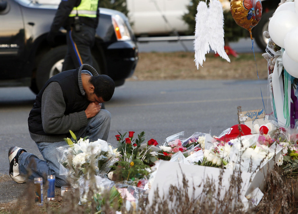 Photo - A mourner pays his respects at a memorial for shooting victims near Sandy Hook Elementary School, Saturday, Dec. 15, 2012 in Newtown, Conn.  A gunman walked into Sandy Hook Elementary School in Newtown Friday and opened fire, killing 26 people, including 20 children. (AP Photo/Jason DeCrow) ORG XMIT: CTJD117