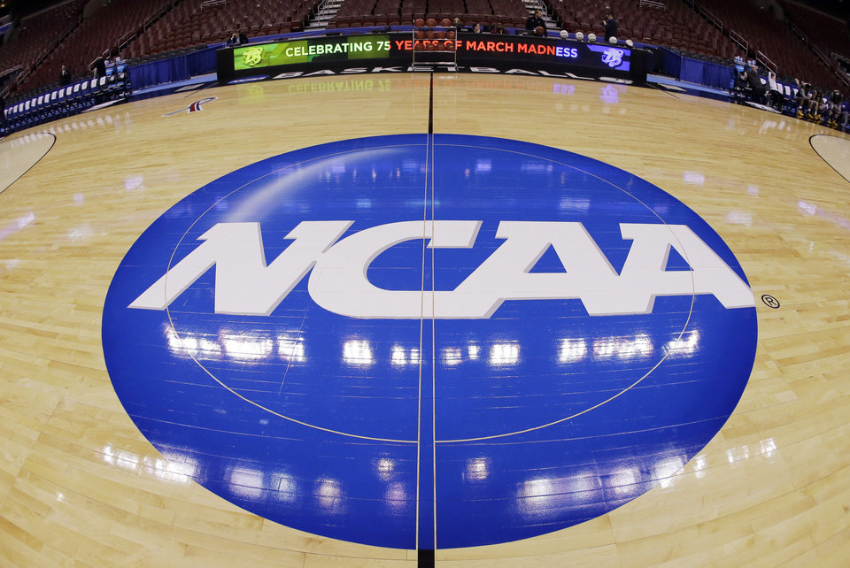 Photo - FILE - In this March 21, 2013, file photo, in this image taken with a fisheye lens, the NCAA logo is displayed at mid-court before Albany's practice for a second-round game of the NCAA college basketball tournament in Philadelphia. Barely a month ago, the NCAA was shamed into apologizing for trying to rig its own investigation into funny business at the University of Miami. According to a new report, that apology didn't go nearly far enough. (AP Photo/Matt Slocum, File)