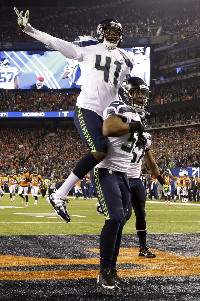 Photo - Seattle Seahawks' Byron Maxwell, top, celebrates with teammate Malcolm Smith after Smith scored a touchdown during the first half of the NFL Super Bowl XLVIII football game Sunday, Feb. 2, 2014, in East Rutherford, N.J. (AP Photo/Mark Humphrey)