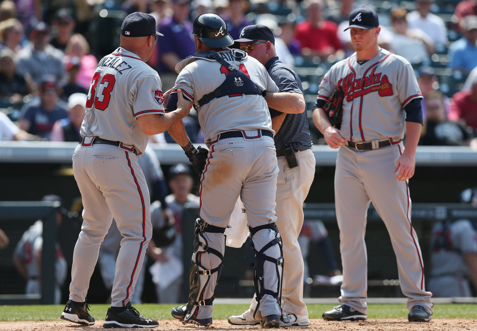 Photo - Atlanta Braves manager Fredi Gonzalez, left, helps catcher Gerald Laird, center, off the field with trainer Jeff Porter as relief pitcher David Carpenter looks on against the Colorado Rockies in the eighth inning of the Rockies' 10-3 victory in a baseball game in Denver on Thursday, June 12, 2014. Laird was hit in the face by rockies batter Corey Dickerson as he was swinging at a pitch. The play acted as a catalyst for the ejection of Rockies' manager Walt Weiss after Dickerson was hit by a pitch when action resumed. (AP Photo/David Zalubowski)