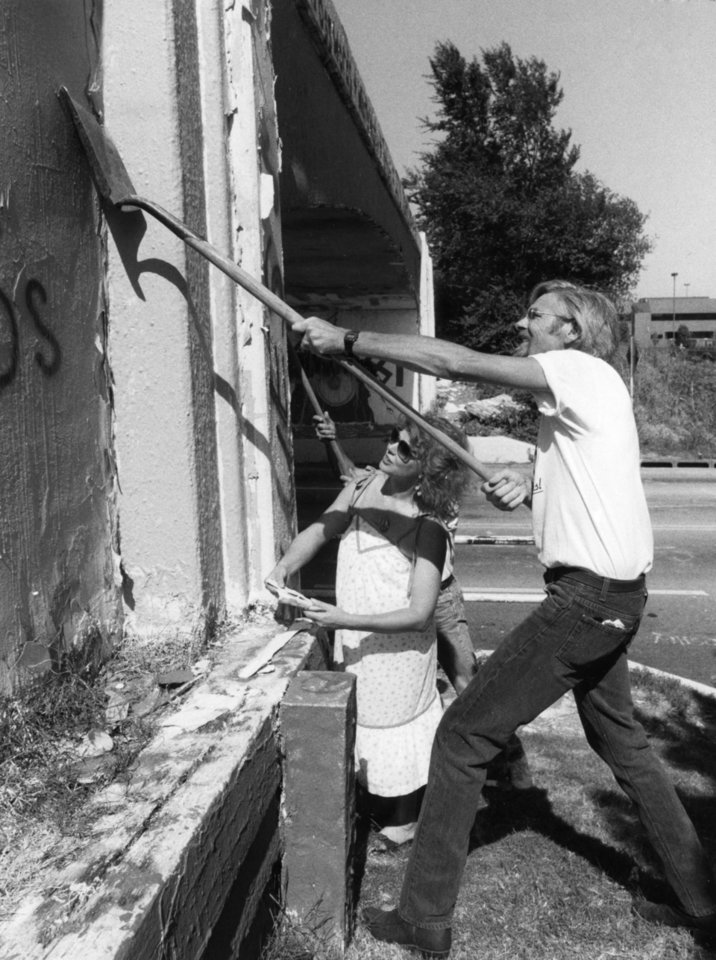 Photo - Colorful markings from the graffiti bridge will become a memory after this week.  Tommie Gatewood and Randy Feuerborn use a shovel to scrape the remaining paint pieces off the bridge.  Staff photo by Paul Hellstern.  Photo dated 06/21/1991 and published on 06/26/1991 in The Daily Oklahoman(N).