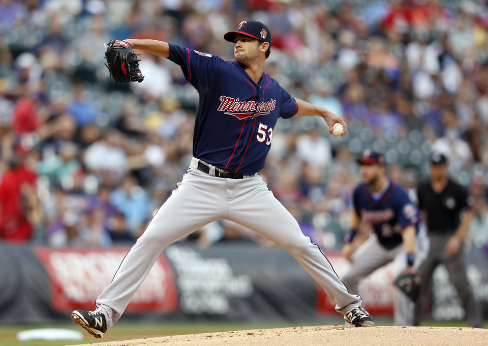 Photo - Minnesota Twins starting pitcher Kris Johnson throws to the plate against the Colorado Rockies during the first inning of a baseball game on Friday, July 11, 2014, in Denver. (AP Photo/Jack Dempsey)