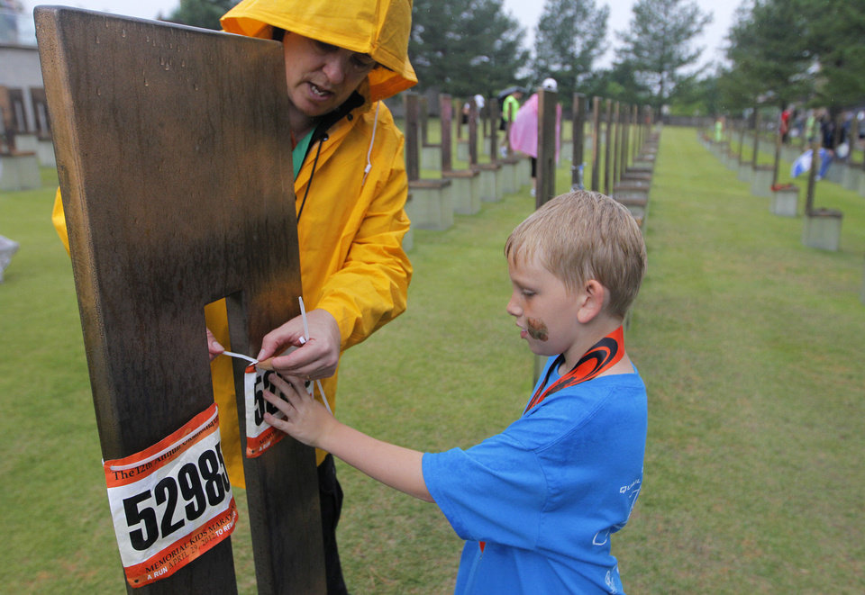 Helen Steifmiller, a museum curator, helps Blake Bussey, 7, of Oklahoma City, attach his bib to a chair at the Oklahoma City Memorial during the twelfth annual Oklahoma City Memorial Marathon in Oklahoma City, Sunday, April 29, 2012.  Photo by Garett Fisbeck, For The Oklahoman