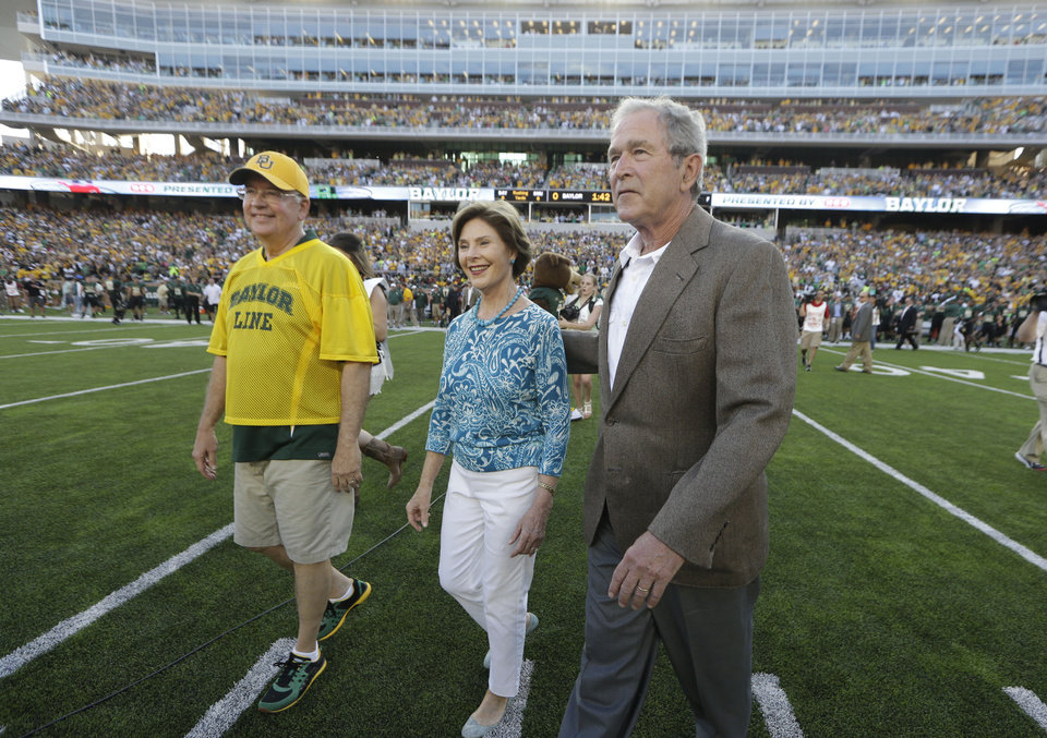 Photo - Former President George W. Bush, right, walks on the field with his wife Laura Bush and Baylor President Ken Starr for the coin toss before the NCAA college football game between SMU and Baylor Sunday, Aug. 31, 2014, in Waco, Texas. (AP Photo/LM Otero)