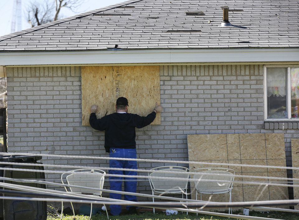 Photo - A man covers broken windows on this house with large sheets of plywood. Neighborhood  between NW 5 and Main Street, and between Telephone Rd. and Santa Fe in Moore.  Thursday morning, March 26, 2015, the day after a tornado damaged homes and a school Wednesday evening. Photo by Jim Beckel, The Oklahoman
