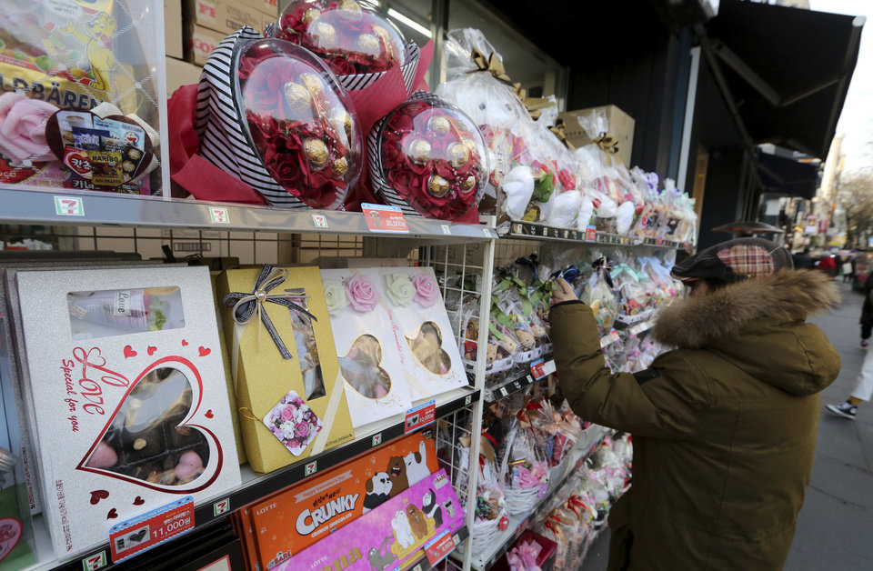 Photo -  A woman browses packages of chocolates and toys on sale for Valentine's Day. [AP PHOTO]