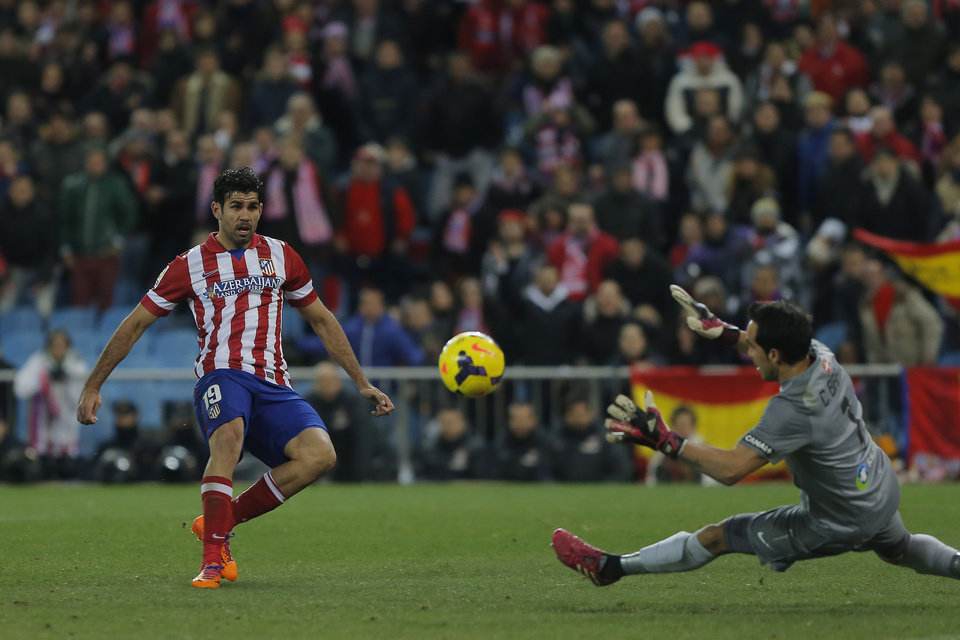 Photo - Atletico's Diego Costa, left, scores his goal during a Spanish La Liga soccer match between Atletico de Madrid and  Real Sociedad at the Vicente Calderon stadium in Madrid, Spain, Sunday, Feb. 2, 2014. (AP Photo/Andres Kudacki)