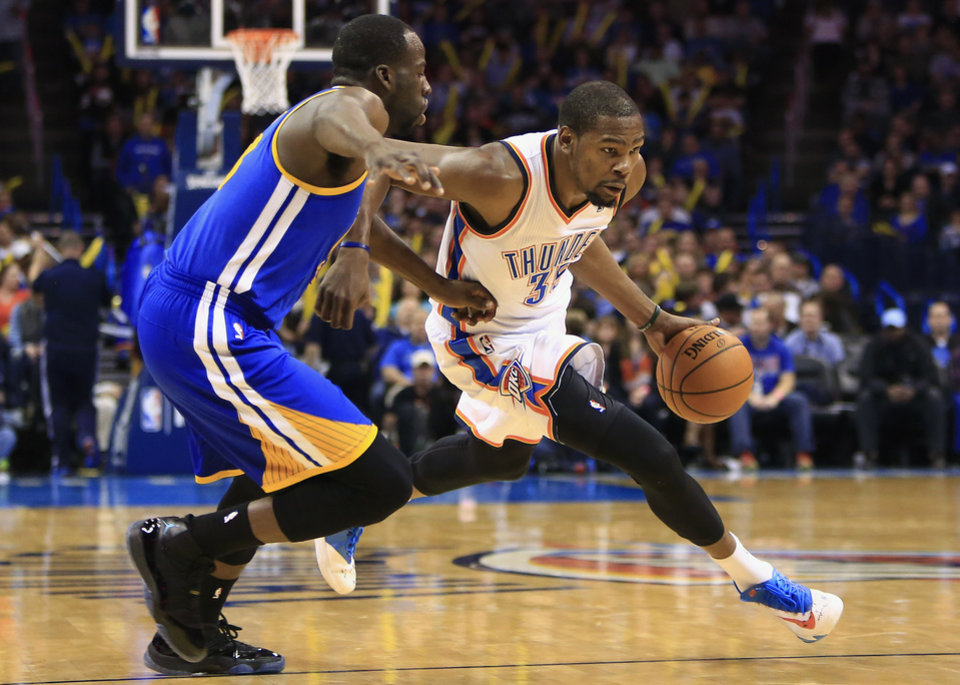 Photo - Oklahoma City Thunder small forward Kevin Durant (35) drives to the basket as Golden State Warriors small forward Draymond Green (23)  defends during the third quarter of an NBA basketball game Friday, Jan. 17, 2014, in Oklahoma City. (AP Photo/Alonzo Adams)