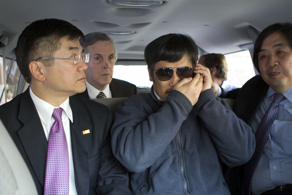 Photo -   In this photo released by the US Embassy Beijing Press Office, blind lawyer Chen Guangcheng, center, accompanied by U.S. ambassador to China, Gary Locke, left, talks on a cell phone in a car en route from the U.S. Embassy to a hospital in Beijing, Wednesday, May 2, 2012. At second left is language attache James Brown and at right is U.S. State Department legal advisor Harold Koh. (AP Photo/U.S. Embassy Beijing Press Office, HO)