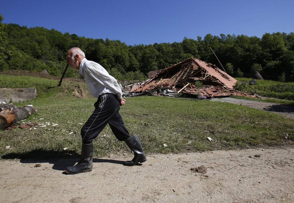 Photo - A Bosnian man passes a house destroyed in a landslide near Tuzla, 140 kms north of Sarajevo, on Monday May 19, 2014. Three months' worth of rain fell on the Balkan region in three days, producing the worst floods since rainfall measurements began 120 years ago. (AP Photo/Amel Emric)
