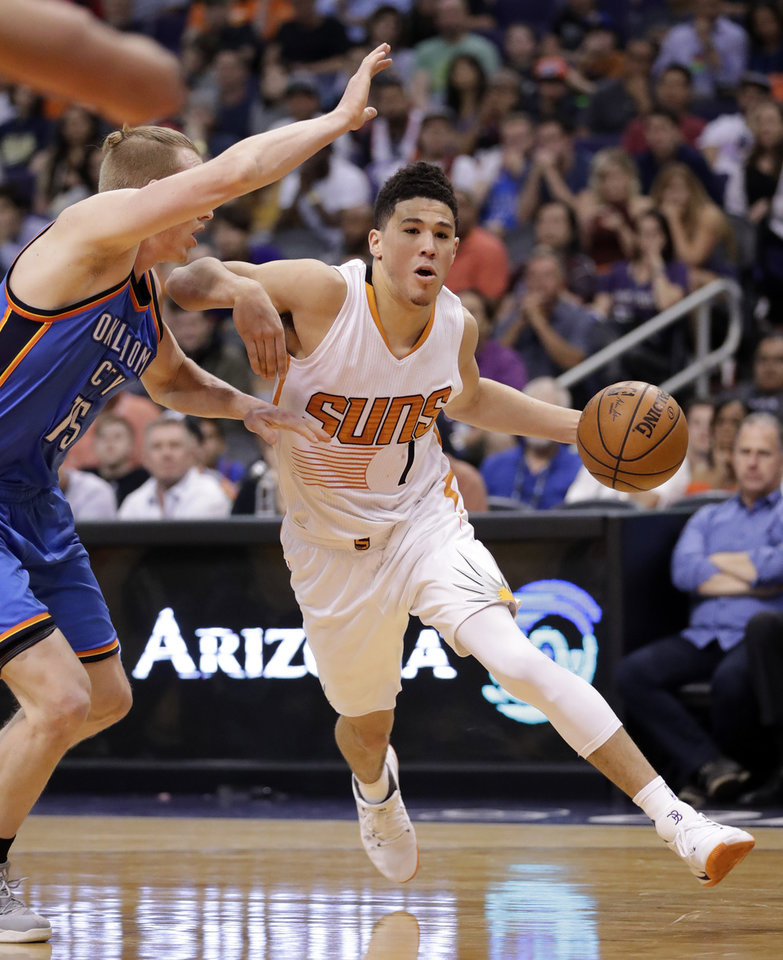 Photo - Phoenix Suns guard Devin Booker (1) drives past Oklahoma City Thunder forward Kyle Singler during the second half of an NBA basketball game, Friday, April 7, 2017, in Phoenix. The Suns won 120-99. (AP Photo/Matt York)