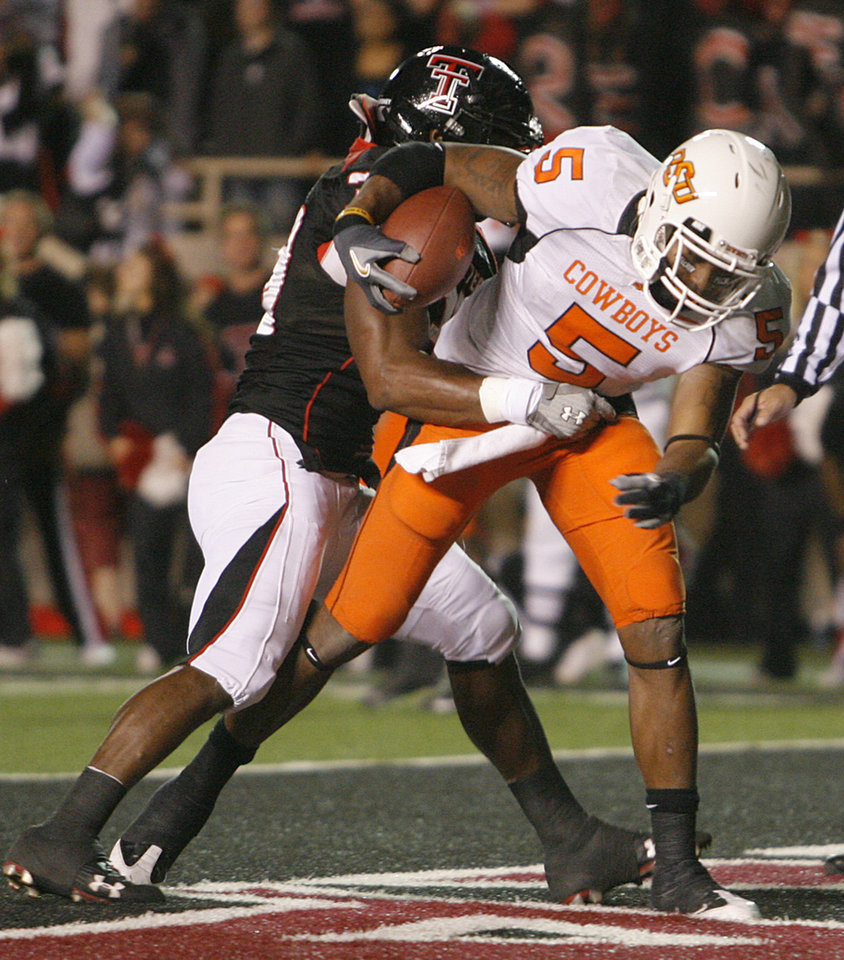 Photo - Oklahoma State's Ketih Toston (5) drags Texas Tech's Jordy Rowland (39) into the end zone for a touchdown during the first half of the college football game between the Oklahoma State University Cowboys (OSU) and the Texas Tech Red Raiders at Jones AT&T Stadium on Saturday, Nov. 8, 2008, in Lubbock, Tex.BY CHRIS LANDSBERGER/THE OKLAHOMAN