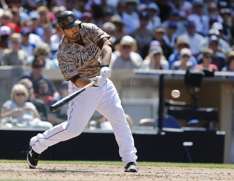 Photo - San Diego Padres pinch hitter Carlos Quentin slams a base hit to left to bring in the go ahead run against the Chicago Cubs during the sixth inning of a baseball game Sunday, May 25, 2014, in San Diego. Quentin hit a two-run home run pinch hitting in the last game. (AP Photo/Lenny Ignelzi)
