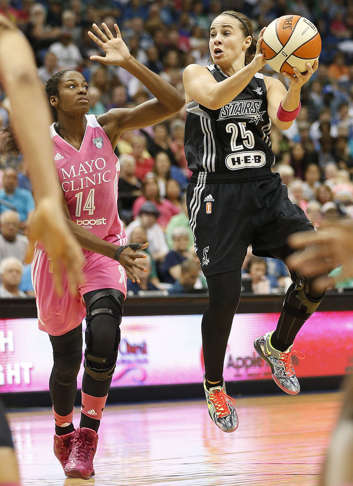 Photo - San Antonio Stars guard Becky Hammon (25) looks to pass the ball against Minnesota Lynx forward Devereaux Peters (14) in the second half of a WNBA basketball game, Friday, July 25, 2014, in Minneapolis. The Lynx won 88-78. (AP Photo/Stacy Bengs)