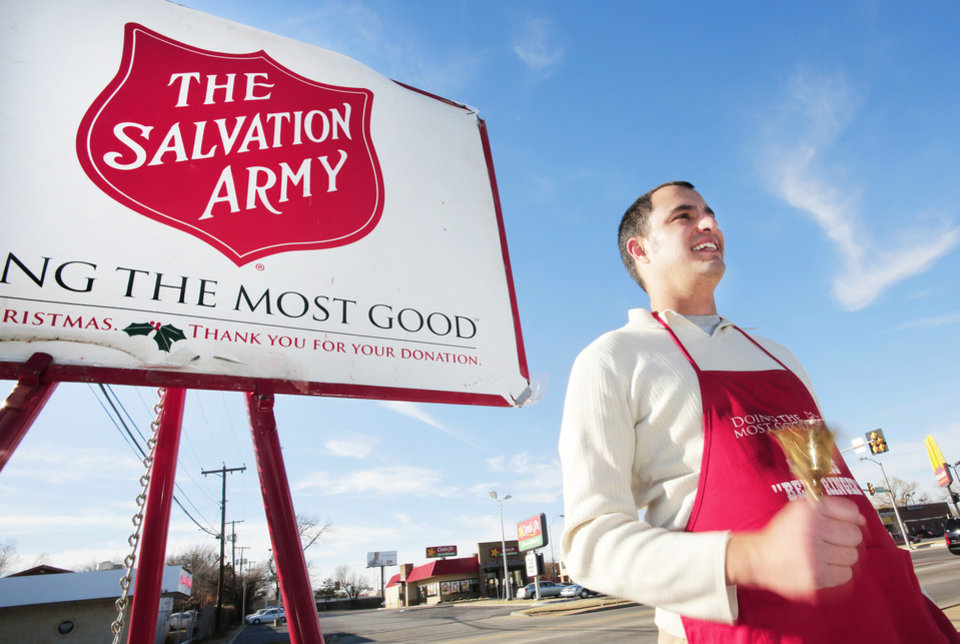 Photo - Salvation Army volunteer Adam Bush rings a bell while taking donations outside Byrons Liquor Store in Oklahoma City, Tuesday December 18, 2012. Photo By Steve Gooch, The Oklahoman