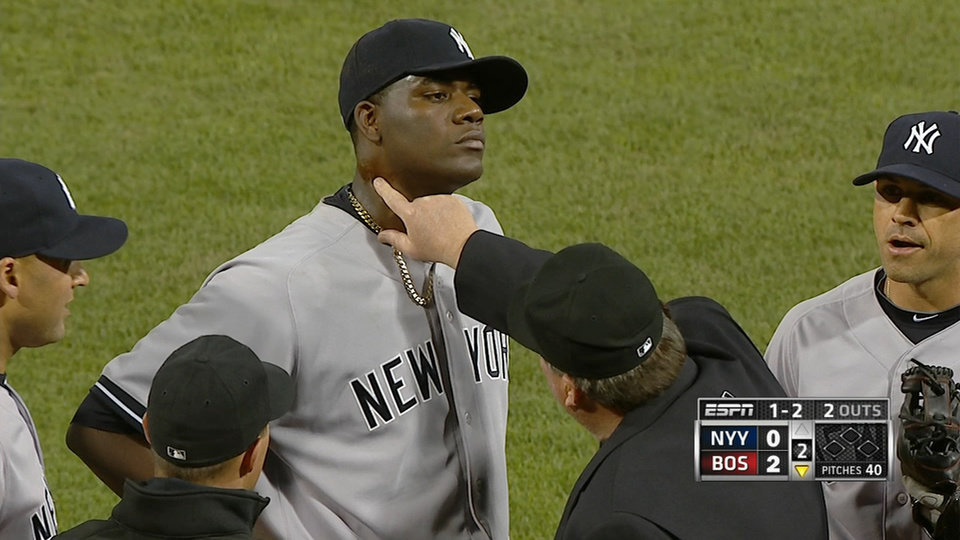 Photo - In this April 23, 2014 photo taken from video and provided by ESPN, home plate umpire Gerry Davis touches the neck of New York Yankees starting pitcher Michael Pineda in the second inning of the Yankees' baseball game against the Boston Red Sox at Fenway Park in Boston. Pineda was ejected after umpires found a foreign substance on his neck. (AP Photo/ESPN)