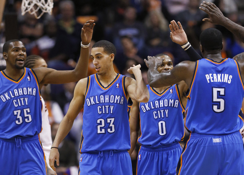 Oklahoma City Thunder's Kevin Durant (35), Kevin Martin (23), Russell Westbrook (0) and Kendrick Perkins high-five during the second half of an NBA basketball game against the Phoenix Suns, Monday, Jan. 14, 2013, in Phoenix. The Thunder won 102-90. (AP Photo/Matt York) ORG XMIT: PNU112
