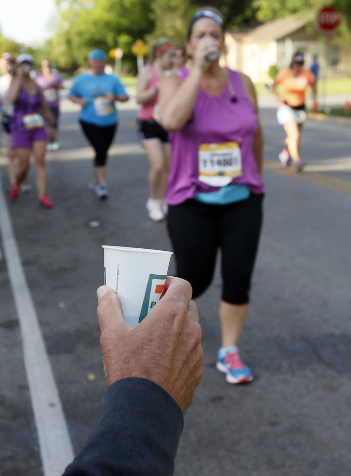 Photo - A volunteer holds out a cup of Powerade for runners at the Westminster Presbyterian Church water stop during the Oklahoma City Memorial Marathon in Oklahoma City, Sunday, April 24, 2016. Photo by Nate Billings, The Oklahoman