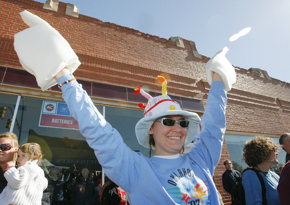 Photo - Elaine Fite, from Stillwater, holds up her Oklahoma foam fingers she made in the shape of Oklahoma as she watches the Centennial parade go by, Friday, November 16, 2007.  By David McDaniel, The Oklahoman