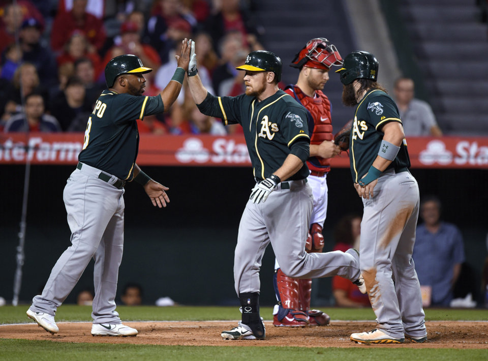 Photo - Oakland Athletics' Brandon Moss, second from left, is congratulated by Alberto Callaspo, left, and Derek Norris, right, after hitting a three-run home run, as Los Angeles Angels catcher Chris Iannetta stands behind them during the fourth inning of a baseball game, Wednesday, April 16, 2014, in Anaheim, Calif. (AP Photo/Mark J. Terrill)