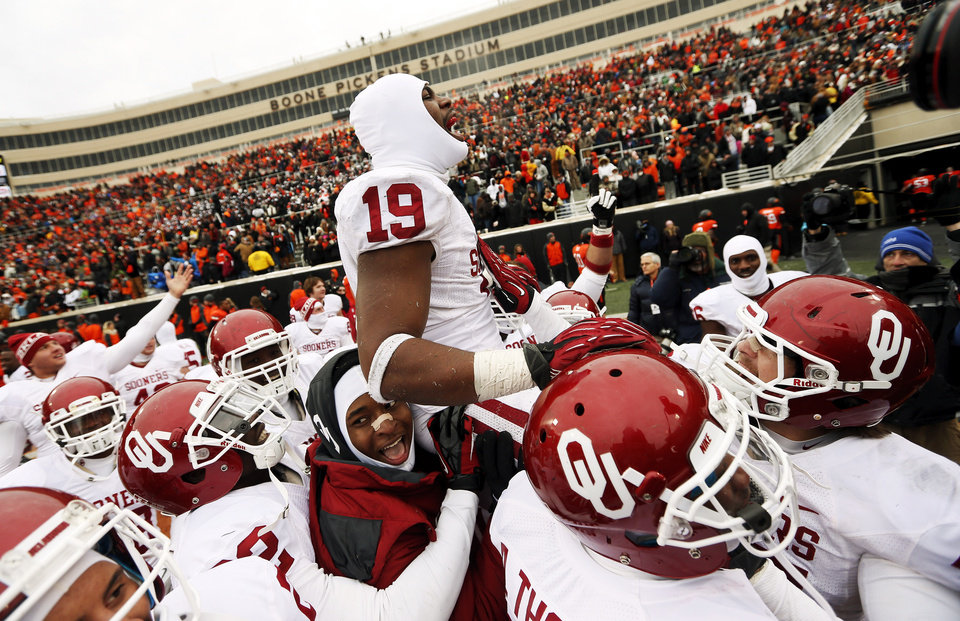 The Sooners lift up Oklahoma\'s Eric Striker (19) as they celebrate after Striker scored a touchdown on a fumble recovery during the final play of the Bedlam college football game between the Oklahoma State University Cowboys (OSU) and the University of Oklahoma Sooners (OU) at Boone Pickens Stadium in Stillwater, Okla., Saturday, Dec. 7, 2013. OU won, 33-24. Photo by Nate Billings, The Oklahoman