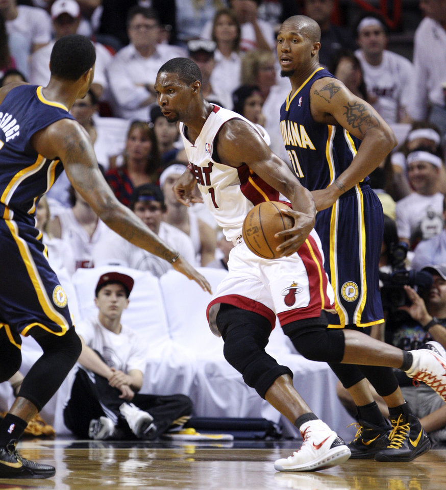 Photo -   Miami Heat forward Chris Bosh, center, drives past Indiana Pacers guard Paul George, left, and forward David West during the first half of Game 1 in an NBA basketball Eastern Conference semifinal playoff series, Sunday, April 13, 2012, in Miami. Bosh was ruled out of the second half of the game because of what the team called a lower abdominal injury. The Heat won 95-86. (AP Photo/Wilfredo Lee)
