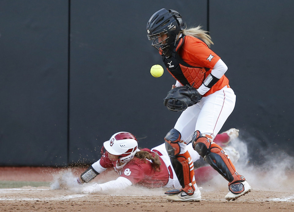 Photo -  Oklahoma's Nicole Mendes (11) slides home as Oklahoma State's Mackenzie Thomas tries to catch the ball in the fifth inning of the Bedlam rivalry in Stillwater on Wednesday [PHOTO BY BRYAN TERRY, THE OKLAHOMAN]