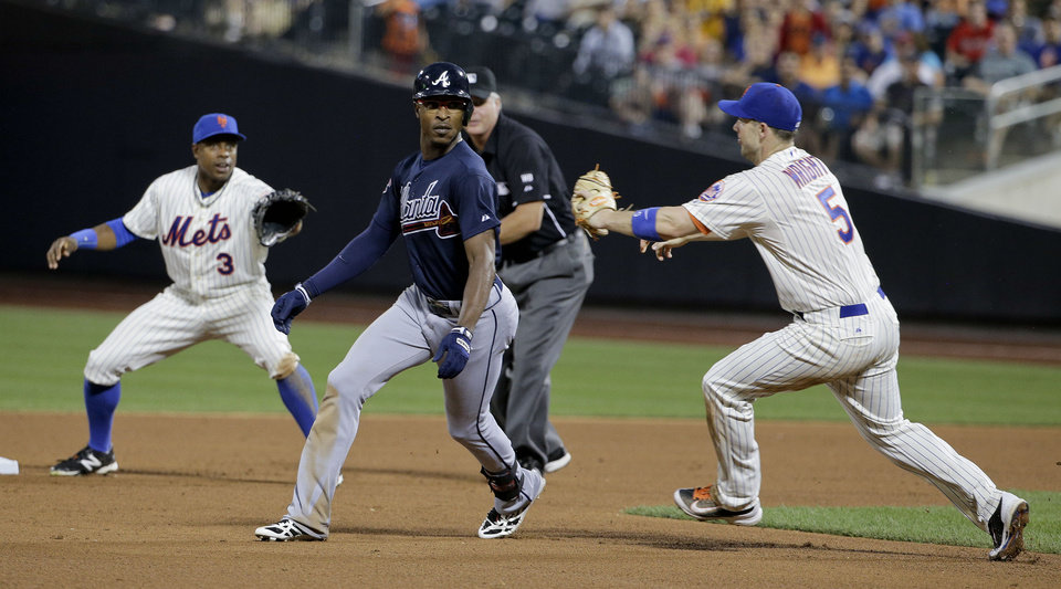 Photo - Atlanta Braves' B.J. Upton, center, is caught in a rundown between New York Mets right fielder Curtis Granderson (3) and third baseman David Wright (5) in the sixth inning of a baseball game, Wednesday, July 9, 2014, in New York. Upton was tagged out on the play to end the inning.(AP Photo/Julie Jacobson)
