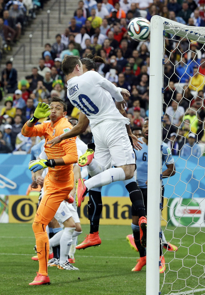 Photo - England's Wayne Rooney hits the bar with a header during the group D World Cup soccer match between Uruguay and England at the Itaquerao Stadium in Sao Paulo, Brazil, Thursday, June 19, 2014. (AP Photo/Thanassis Stavrakis)