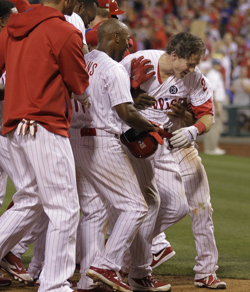 Photo - Philadelphia Phillies' Chase Utley is mobbed by teammates after hitting a two-home run in the 14th inning of a baseball game against the Miami Marlins, Thursday, June 26, 2014, in Philadelphia. The Phillies won 5-3. (AP Photo/Laurence Kesterson)