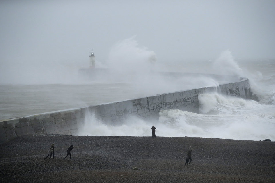 Photo -  Waves crash over the harbour wall by a lighthouse as Storm Ciara hits Newhaven, on the south coast of England, Sunday, Feb. 9, 2020. Trains, flights and ferries have been cancelled and weather warnings issued across the United Kingdom and in northern Europe as the storm with winds expected to reach hurricane levels batters the region. (AP Photo/Matt Dunham)