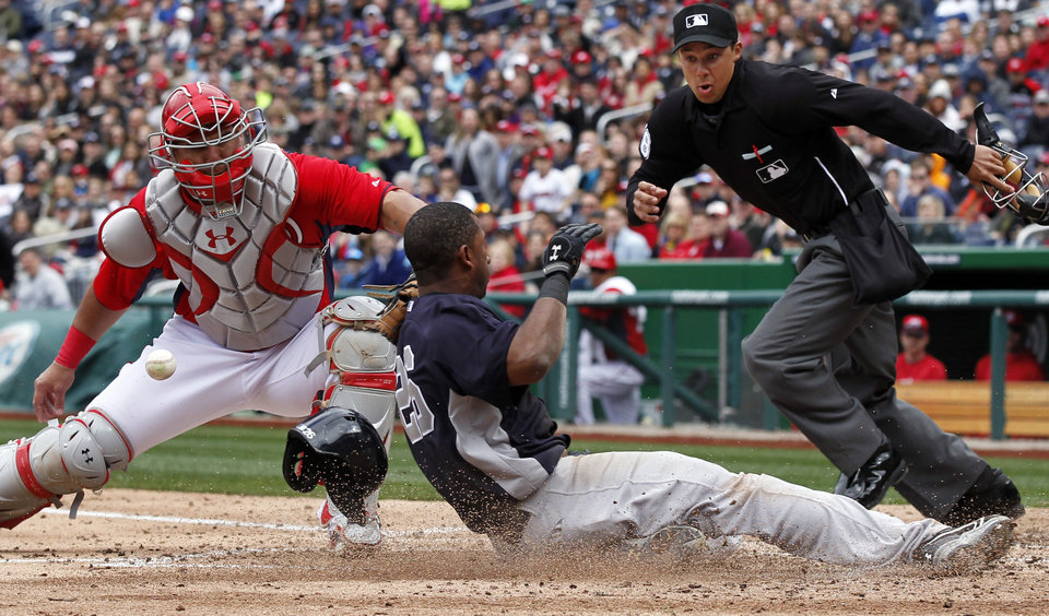 Washington Nationals catcher Wilson Ramos loses the ball as New York Yankees\' Eduardo Nunez slides safely into home with home plate umpire Adam Hamari looking on at right during the fourth inning of an exhibition baseball game at Nationals Park Friday, March 29, 2013, in Washington. (AP Photo/Alex Brandon)