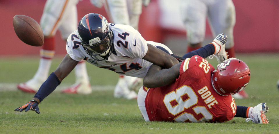Denver Broncos cornerback Champ Bailey (24) breaks up a pass intended for Kansas City Chiefs wide receiver Dwayne Bowe (82) during the second half of an NFL football game on Sunday, Nov. 25, 2012, in Kansas City, Mo. The Broncos won the game 17-9. (AP Photo/Charlie Riedel)