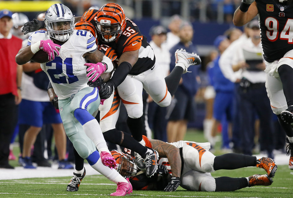 Photo - Dallas' Ezekiel Elliott (21) runs past Cincinnati's Dre Kirkpatrick (27), Vontaze Burfict (55) and Rey Maualuga (58) during an NFL football game between the Dallas Cowboys and the Cincinnati Bengals at AT&T Stadium in Arlington, Texas, Sunday, Oct. 9, 2016. Dallas won 28-14. Photo by Bryan Terry, The Oklahoman