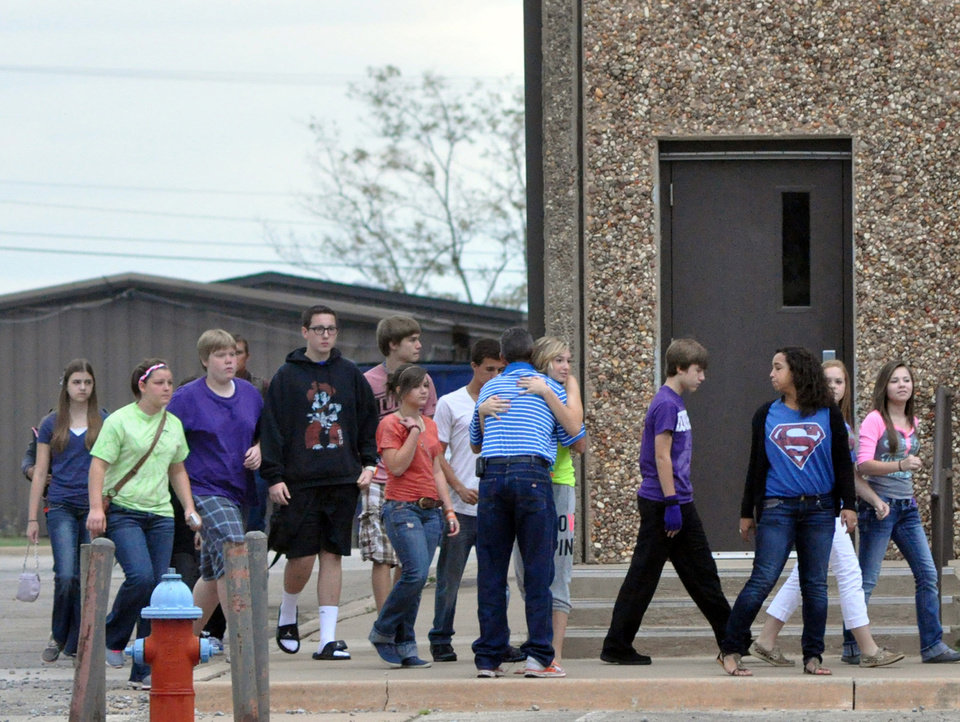Photo - A Stillwater Junior High student hugs a member of the staff as her class is escorted to a waiting bus following the death of a student Wednesday, Sept. 26, 2012 in Stillwater, Okla. A 13-year-old student shot and killed himself in a hallway at an Oklahoma junior high school before classes began Wednesday, police said, terrifying teenagers who feared a gunman was on the loose. (AP Photo/The News Press,Chase Rheam)  ORG XMIT: OKSTI101