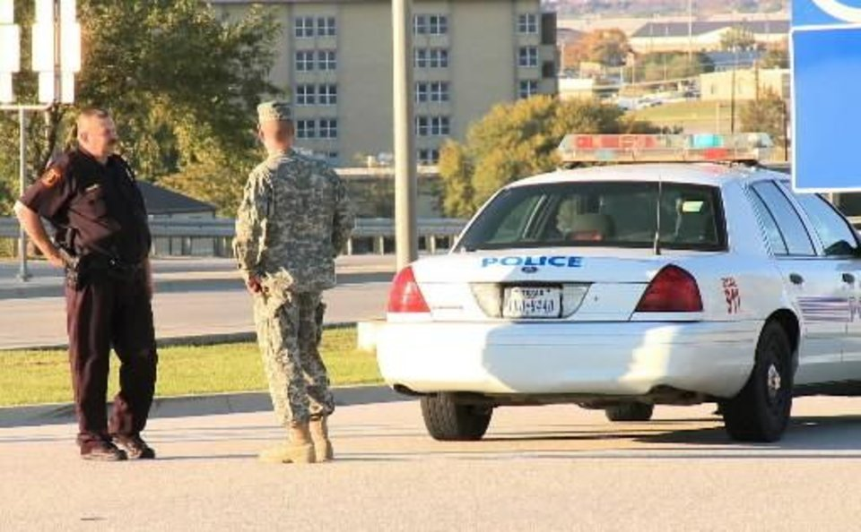 Photo - This still made from video shows a police officer and soldier blocking the road at the main gate of the Army base at  Fort  Hood, Texas on Thursday Nov. 5, 2009. A soldier opened fire at a U.S. Army base in  Fort  Hood, Texas on Thursday, unleashing a stream of gunfire that left 12 people dead and 31 wounded. Authorities killed the gunman, and apprehended two other soldiers suspected in what appears to be the worst mass shooting at a U.S. military base. (AP Photo/Richard Matthews)
