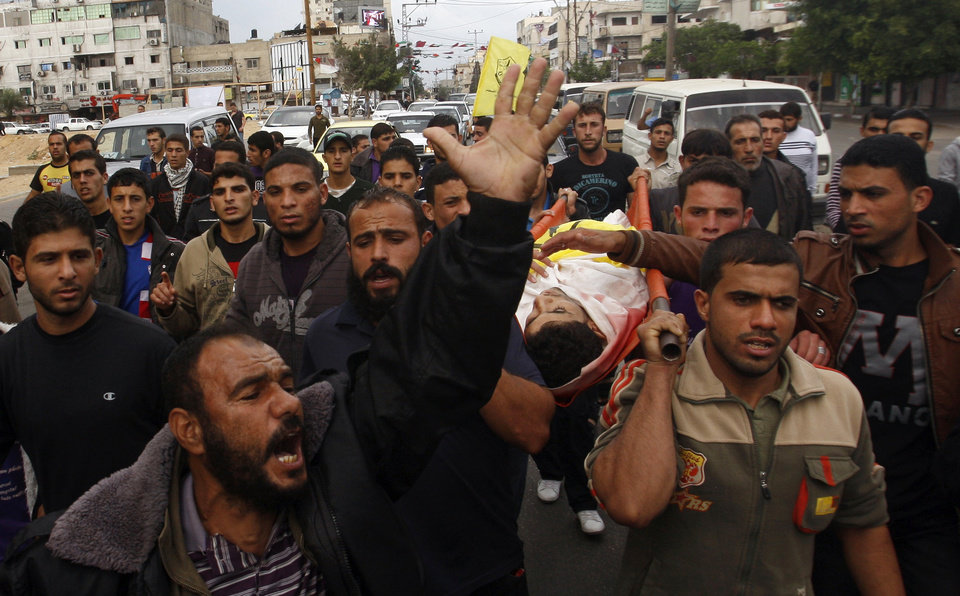 Photo -   Mourners carry the body of Palestinian Matar Abu Ata, 20, killed in a recent Israeli strike, during his funeral in Gaza City, Sunday, Nov. 11, 2012. While cross-border fighting is a common occurrence, hostilities spiraled sharply over the weekend, with bombardments from Gaza causing rare Israeli casualties and Israeli strikes killing at least six Palestinians. (AP Photo/Hatem Moussa)