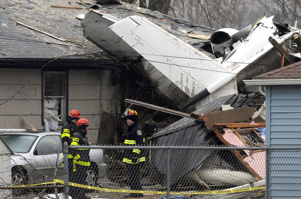 Photo - South Bend firefighters work at the scene, Monday, March 18, 2013, where a plane crashed on Sunday, near the South Bend Regional Airport, in South Bend, Ind. The plane damaged homes, as well as causing injuries. (AP Photo/Joe Raymond)