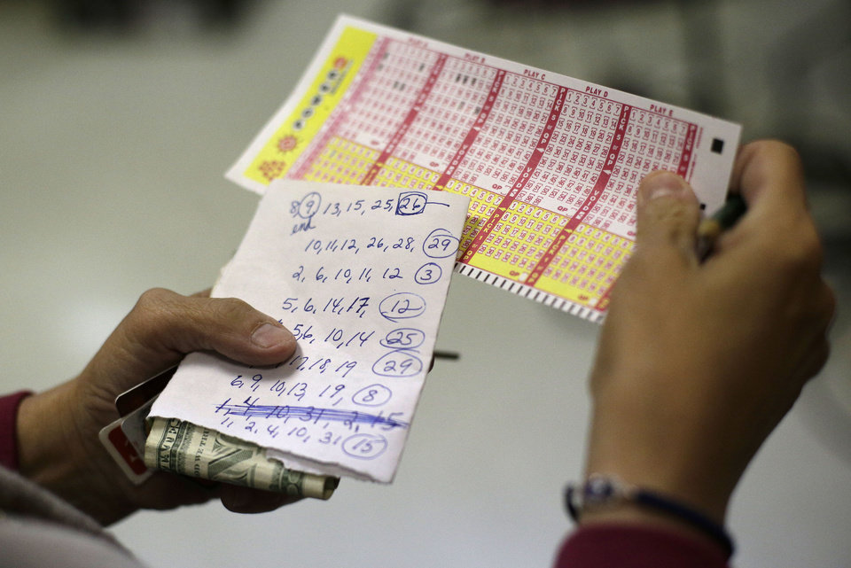 Sharon Long double checks her Powerball numbers as she stands in line in a convenience store in Baltimore, Wednesday, Nov. 28, 2012. Long, a customer service representative for a plumbing company, picked numbers that her sister asked her to play with. If she wins the jackpot with her sister\'s numbers,