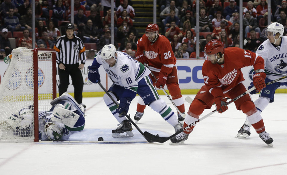 Photo - Detroit Red Wings right wing Patrick Eaves (17) shoots the puck towards Vancouver Canucks goalie Eddie Lack during the second period of an NHL hockey game in Detroit, Monday, Feb. 3, 2014. (AP Photo/Carlos Osorio)
